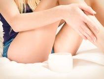 适用于奶油的俏丽的妇女她的腿 免版税库存图片