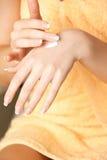 适用于皮肤奶油的妇女手 免版税库存照片