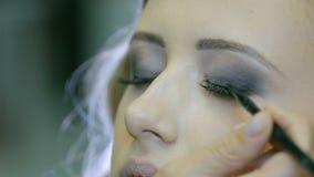 适用于眼睛铅笔和刷子的专业化妆师做的眼皮箭头白肤金发的模型眼皮 股票视频