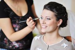 适用婚礼构成的美丽的新娘由化妆师 免版税库存图片