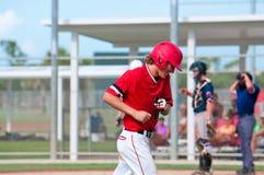 逃跑领域微笑的愉快的青少年的棒球运动员 库存图片