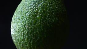 逆时针spining在黑背景的绿色鲕梨的中央部分的特写镜头例证 股票录像