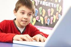 选件类计算机男小学生使用 免版税库存照片