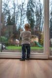 选拔在家站立在一个木地板上的白肤金发的孩子在前面o 免版税库存图片