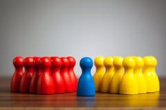 选拔在红色和黄色小组之间的蓝色典当形象 库存照片