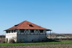 选拔有有趣的木柱墙壁和小山的简单的房子在背景中 外部照片 库存图片