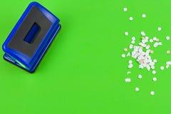 选拔蓝色金属机械打孔器和全部圆的白色五彩纸屑 库存图片