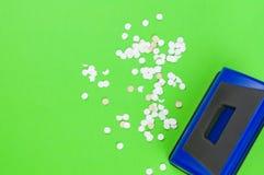选拔蓝色金属机械打孔器和全部圆的白色五彩纸屑 免版税库存照片