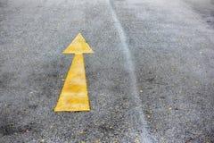 选拔路面上的黄色箭头标志标号 库存图片