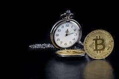选拔金黄bitcoin和怀表在黑背景 库存照片