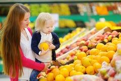 选择一个桔子的母亲和女儿在商店 免版税库存图片