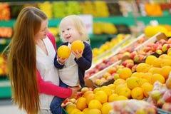 选择一个桔子的母亲和女儿在商店 免版税库存照片
