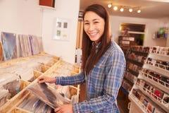 选择一个纪录的妇女在记录商店,画象 图库摄影