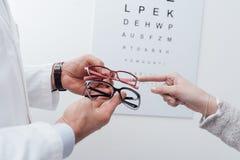 选择一副眼镜的妇女 免版税库存照片
