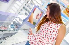 选择一块玻璃的美丽的少妇在陈列室里面的光学商店在被弄脏的背景中 免版税库存照片