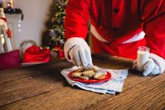 选择与杯的圣诞老人一个曲奇饼牛奶 免版税库存图片