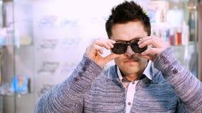选择与透明和黑暗的太阳镜的英俊的年轻人画象镜片特别框架,在光学商店 股票视频
