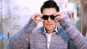 选择与透明和黑暗的太阳镜的英俊的年轻人画象镜片特别框架,在光学商店 股票录像