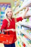 选择个人照料产品的美丽的妇女在超级市场 库存图片
