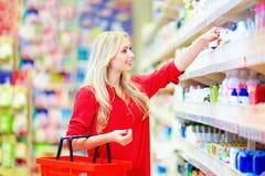 选择个人照料产品的美丽的妇女在超级市场 免版税库存图片