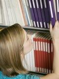 选择书的大学生从架子 免版税库存图片