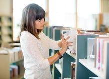 选择书的学生在书店 免版税库存图片