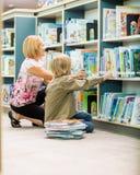 选择书的老师和男孩在图书馆里 库存图片