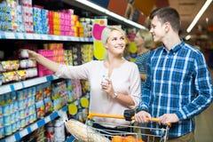选择乳制品和微笑在大型超级市场的家庭 图库摄影