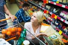 选择乳酪的夫妇在商店 免版税库存照片