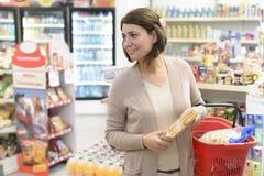 选择产品的顾客在超级市场 免版税库存图片