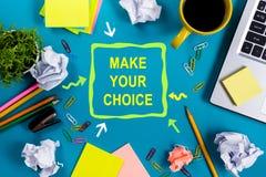 选择做您 办公室有供应的桌书桌,白色空白的笔记本,杯子,笔,个人计算机,弄皱了纸,在蓝色的花 免版税库存图片