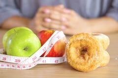 选择健康或不健康吃在苹果和油炸圈饼之间的妇女手 免版税库存图片