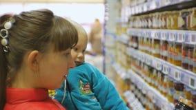 选择儿童食品的可爱的白种人妇女在抱着胳膊的超级市场婴孩 特写镜头看的被射击妈妈 影视素材