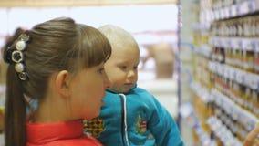 选择儿童食品的可爱的白种人妇女在抱着胳膊的超级市场婴孩 特写镜头采取婴孩的被射击妈妈 股票录像