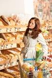 选择副食品商店妇女年轻人的面包 免版税库存照片