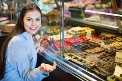 选择可口ganaches、果仁糖和巧克力的微笑的女孩 免版税库存照片