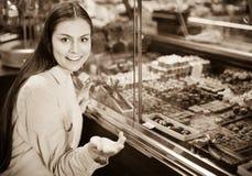 选择可口ganaches、果仁糖和巧克力的微笑的女孩 免版税图库摄影