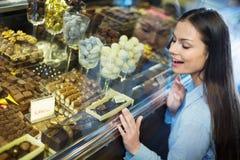 选择可口ganaches和巧克力的美丽的女孩 免版税库存照片