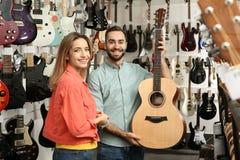 选择吉他的人们在音乐商店 库存图片