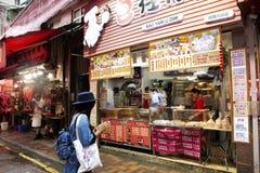 选择和买食物从地方餐馆的旅客泰国妇女在香港,中国 免版税图库摄影