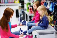年轻选择和尝试在新的雨靴的母亲和她的两个小女孩 免版税图库摄影