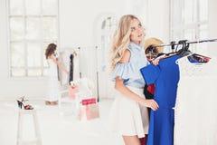 选择和尝试在礼服的年轻俏丽的女孩在商店 库存照片