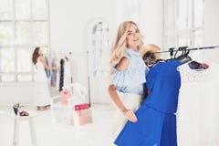 选择和尝试在礼服的年轻俏丽的女孩在商店 库存图片