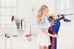 选择和尝试在礼服的年轻俏丽的女孩在商店 免版税图库摄影