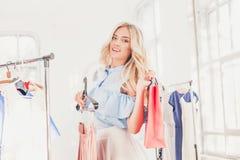 选择和尝试在礼服的年轻俏丽的女孩在商店 免版税库存照片