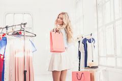 选择和尝试在礼服的年轻俏丽的女孩在商店 免版税库存图片