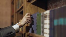 选择和采摘书的男性右手在公立图书馆里 拉扯选择的课本 教育研究和自已 股票录像