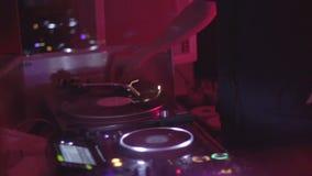 选择唱片的女性DJ演奏在一个转盘的音乐在夜总会 股票录像