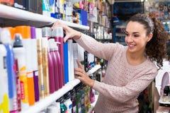 选择喷发剂的妇女在超级市场 免版税图库摄影