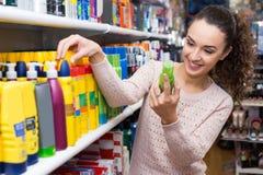 选择喷发剂的妇女在超级市场 图库摄影